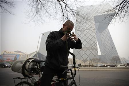 Artist Matt Hope adjusts the helmet linked to his air filtration bike in front of the China Central Television (CCTV) building on a hazy day in Beijing, March 26, 2013. Photo: Petar Kujundzic